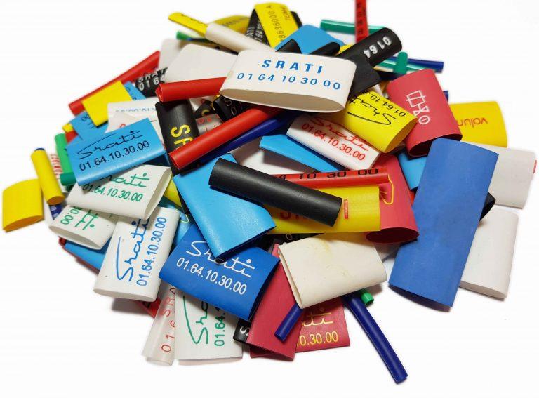 Ensemble de gaines thermorétractables de différents diamètres, couleurs et matériaux. Disposées en tas.
